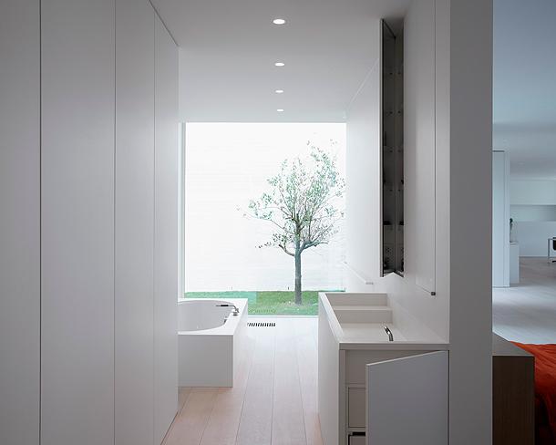 Baño Vestidor Minimalista: vestidor detrás del cabecero de la cama, dos habitaciones y otro